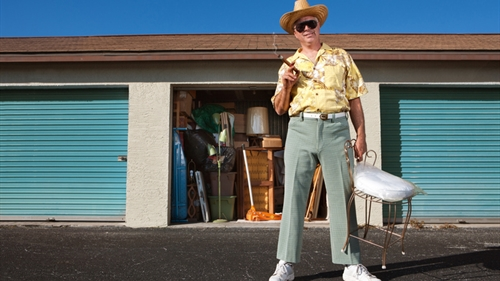 A man in a yellow shirt and white hat holding a chair in front of a storage unit.