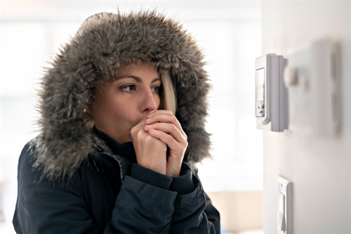 A woman indoors near a thermostat. She is wearing a parka with a fur-lined hood and blows on her hands to warm them.