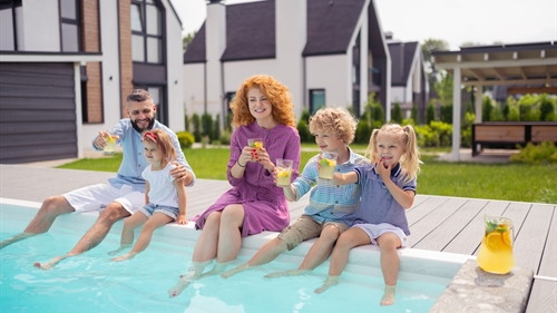 A family sitting on the side of a garden swimming pool dangling their legs in the water
