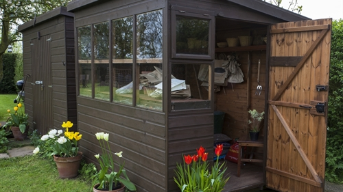 A classy brown shed with windows and a welcoming open door